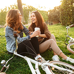 Two women with bikes and coffee in park